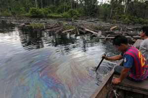 CUNINICO, Peru–Villager examine oil slick near this Kukama Indian village in the northeastern Peruvian Amazon. Photo by Barbara Fraser.